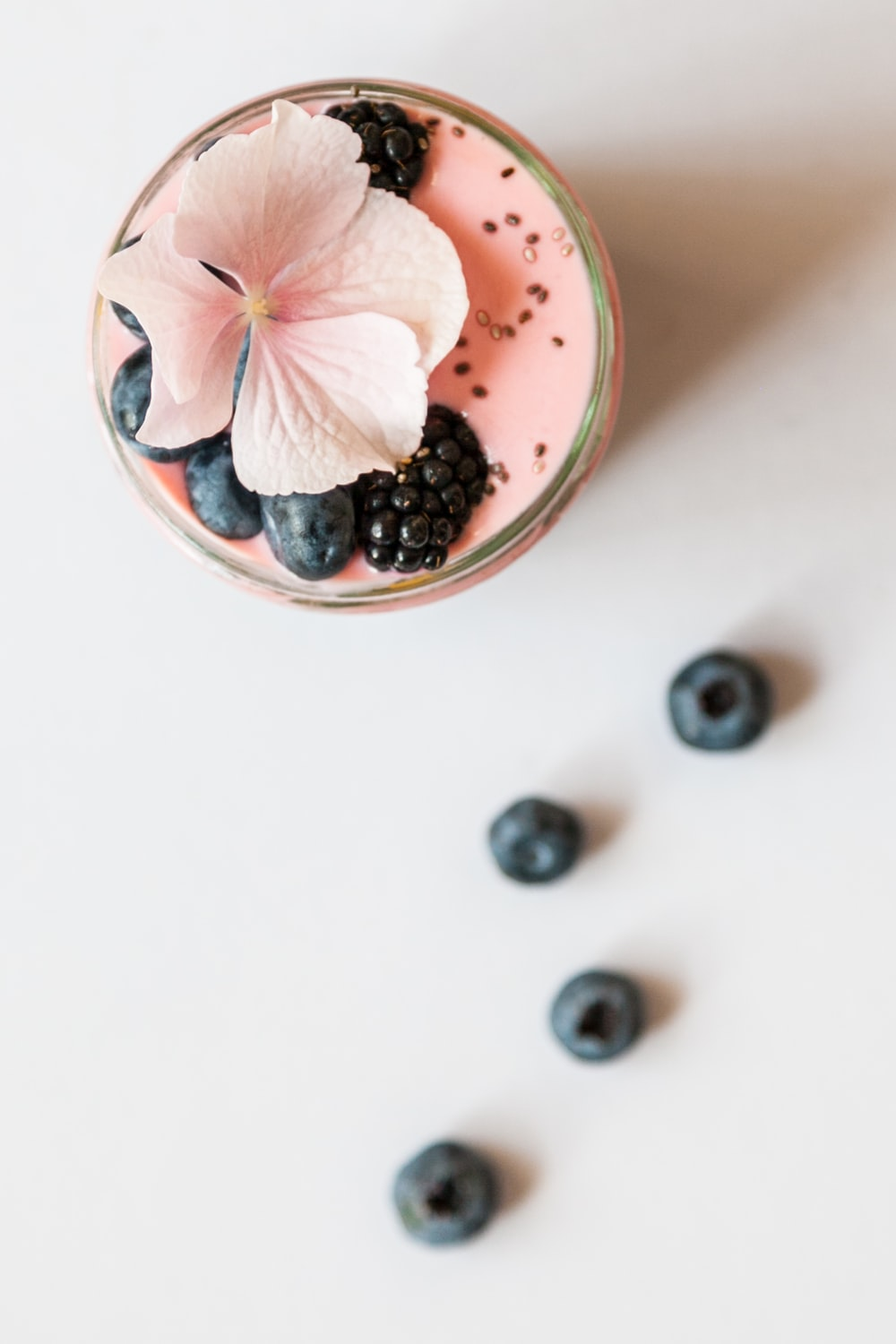pink beverage on glass with blackberries and pink flower on top