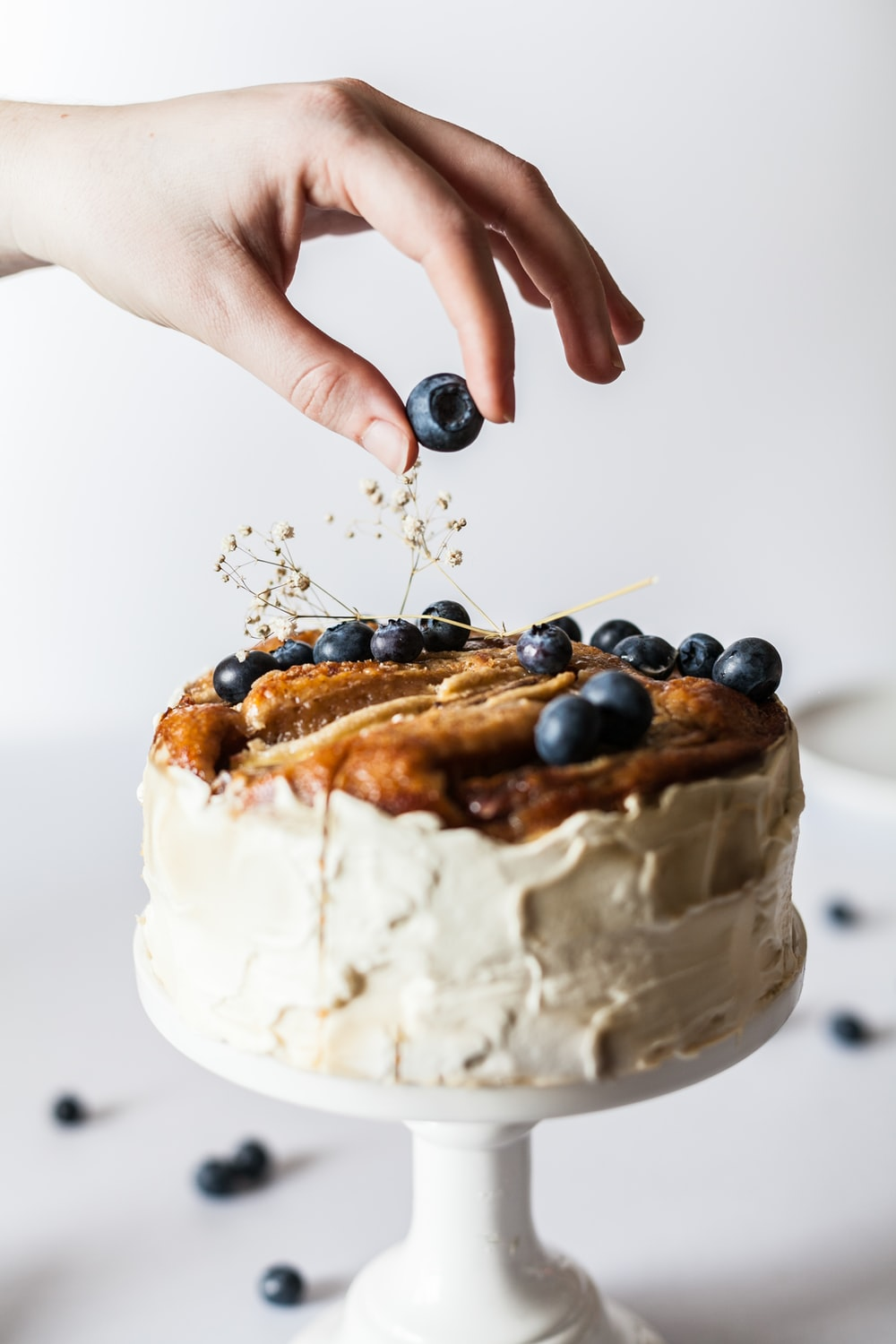 person holding black fruit near cake