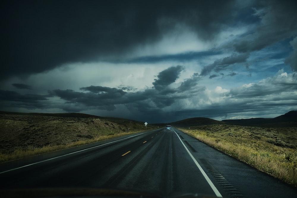 asphalt road near field under white clouds