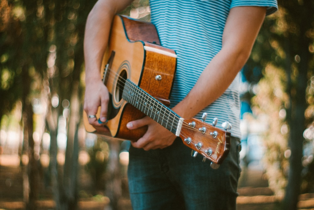 person holding acoustic guitar