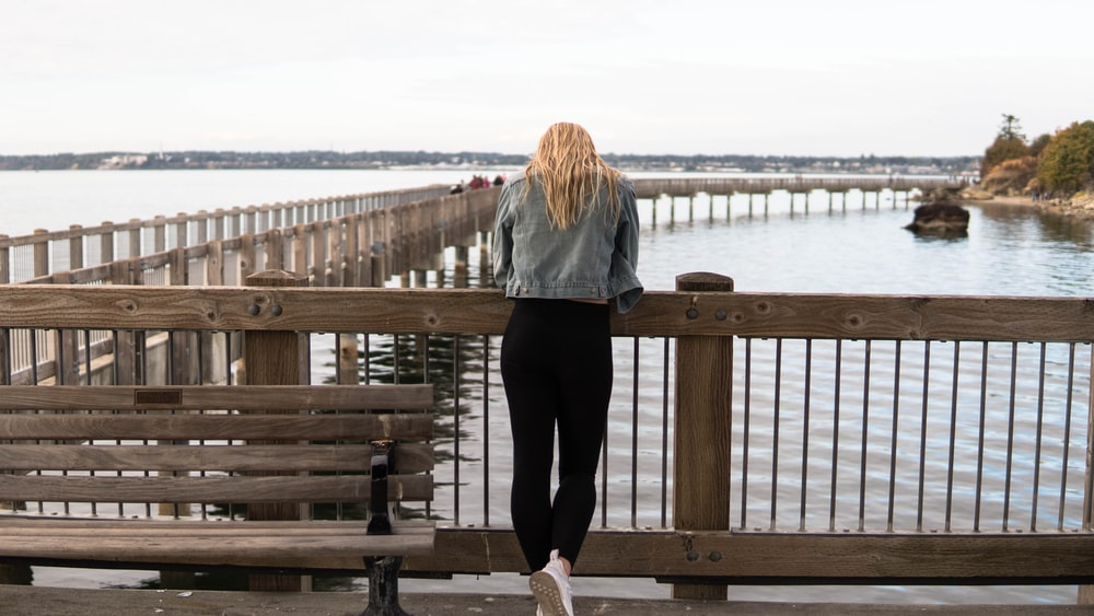 woman in gray jacket and black pants standing on brown wooden dock during daytime