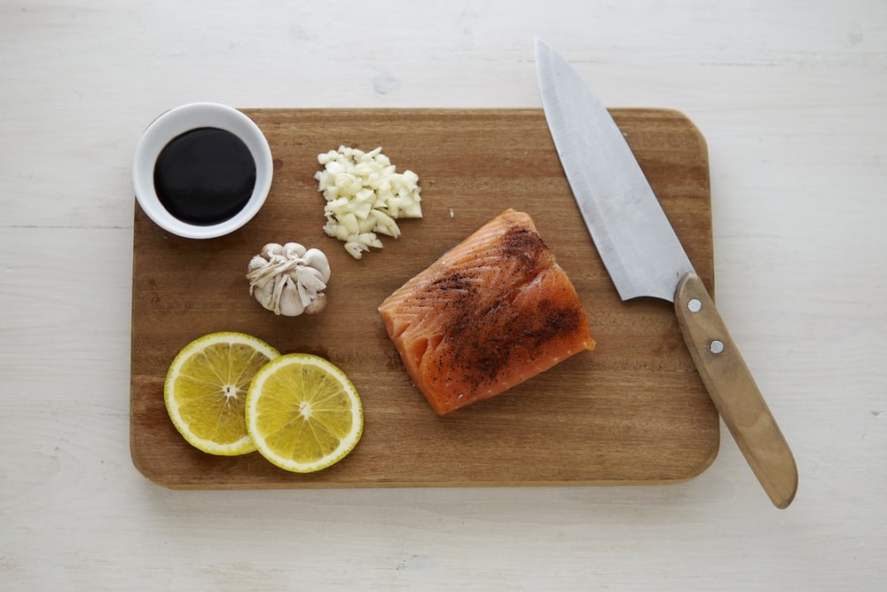 gray knife and orange flesh meat on wooden chopping board