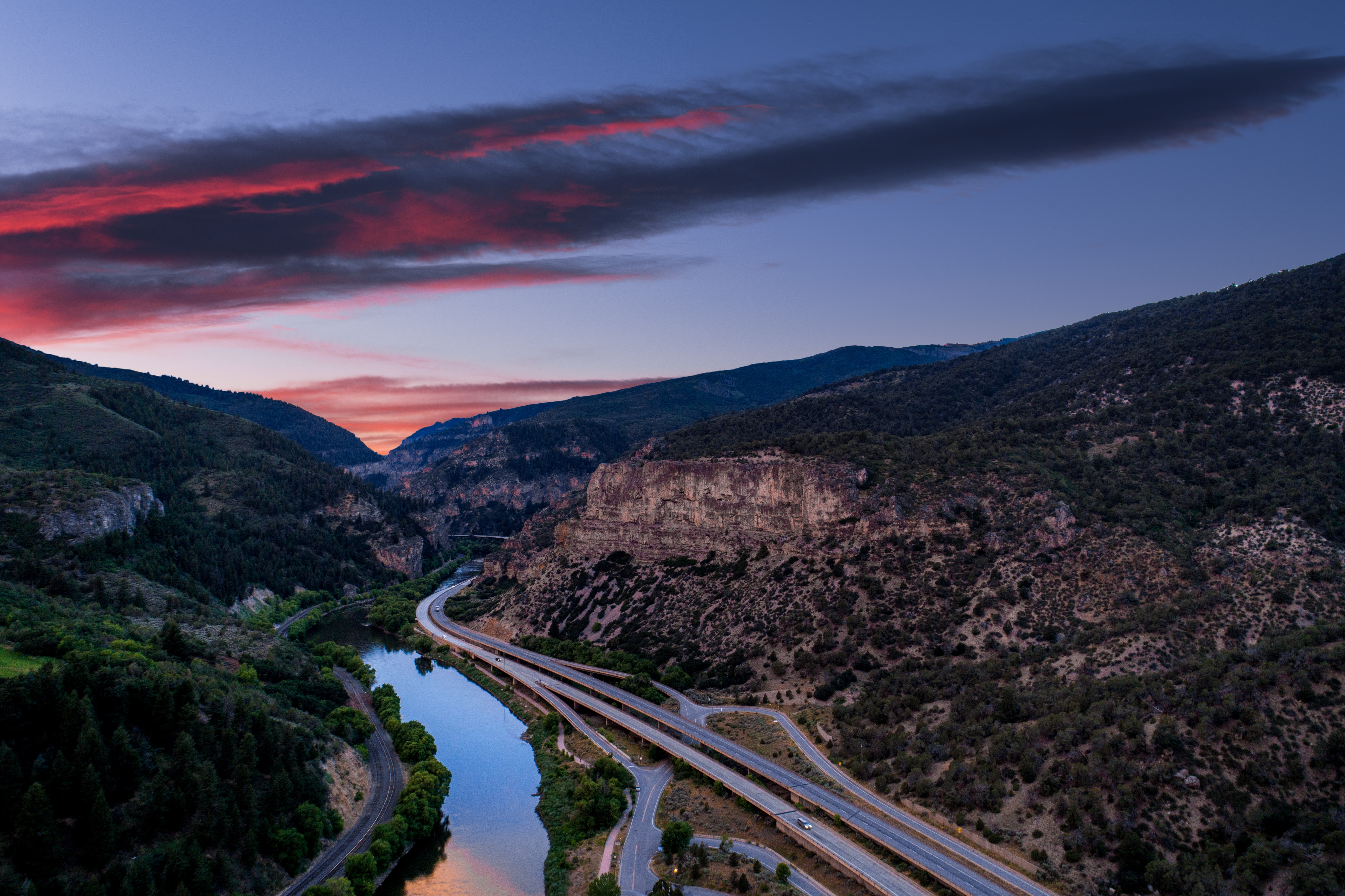 aerial photography of concrete road near river and mountain during sunset