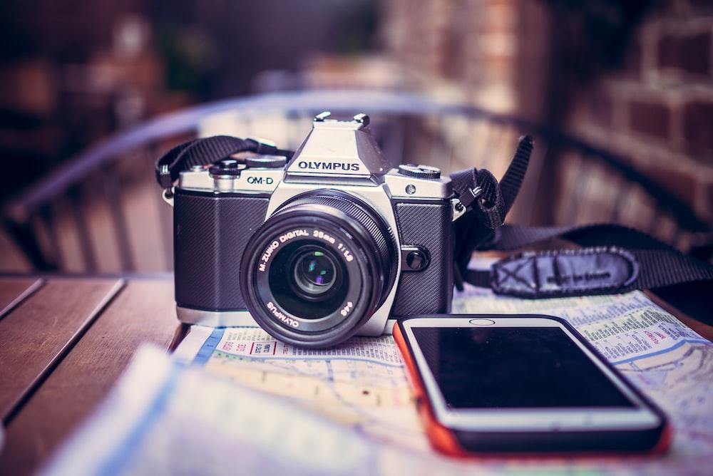 black Olympus SLR camera near white iPhone