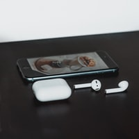 space gray iPhone 6 and Apple AirPods with case on black wooden table