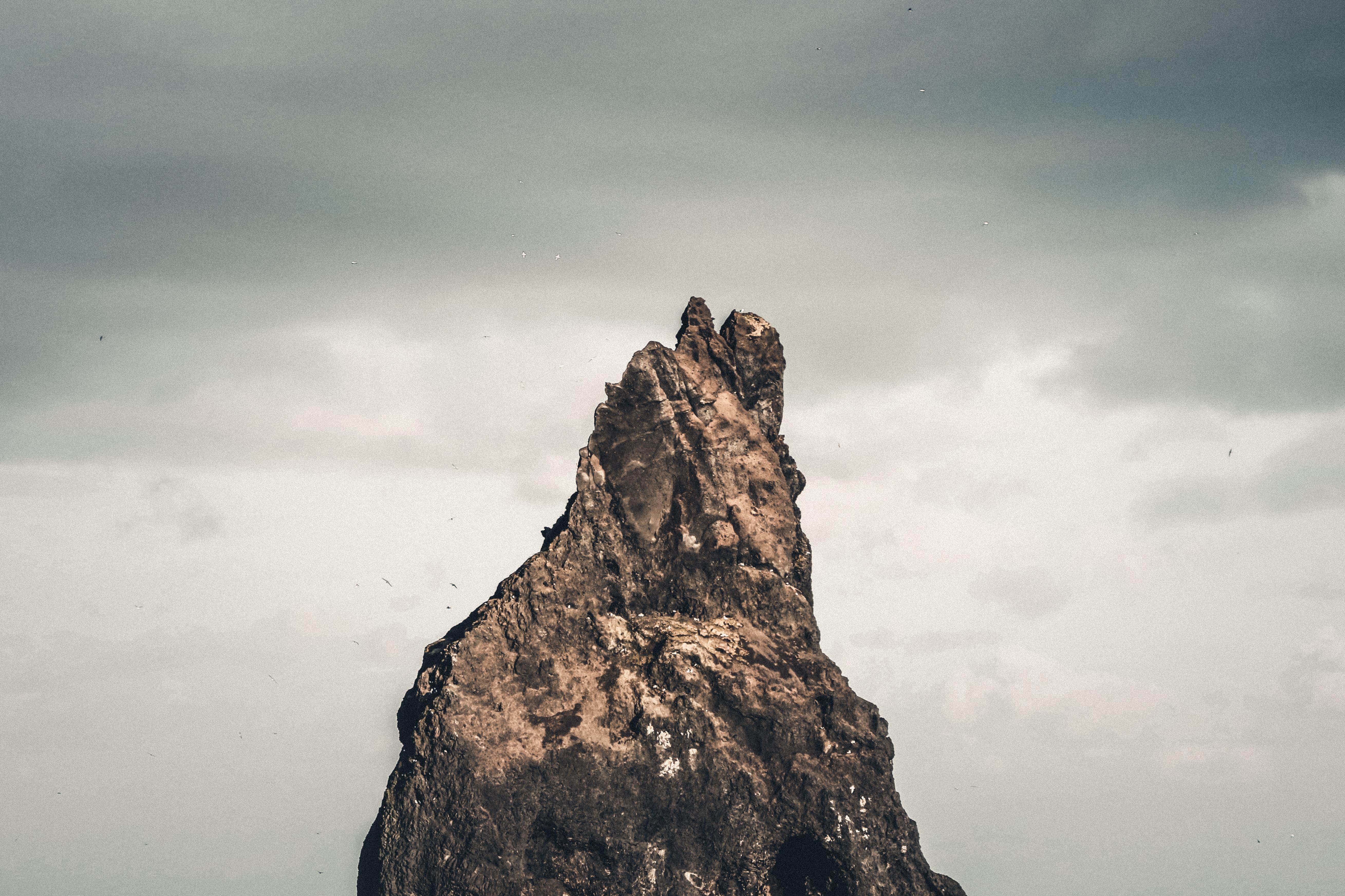 rocky mountain peak under cloudy sky