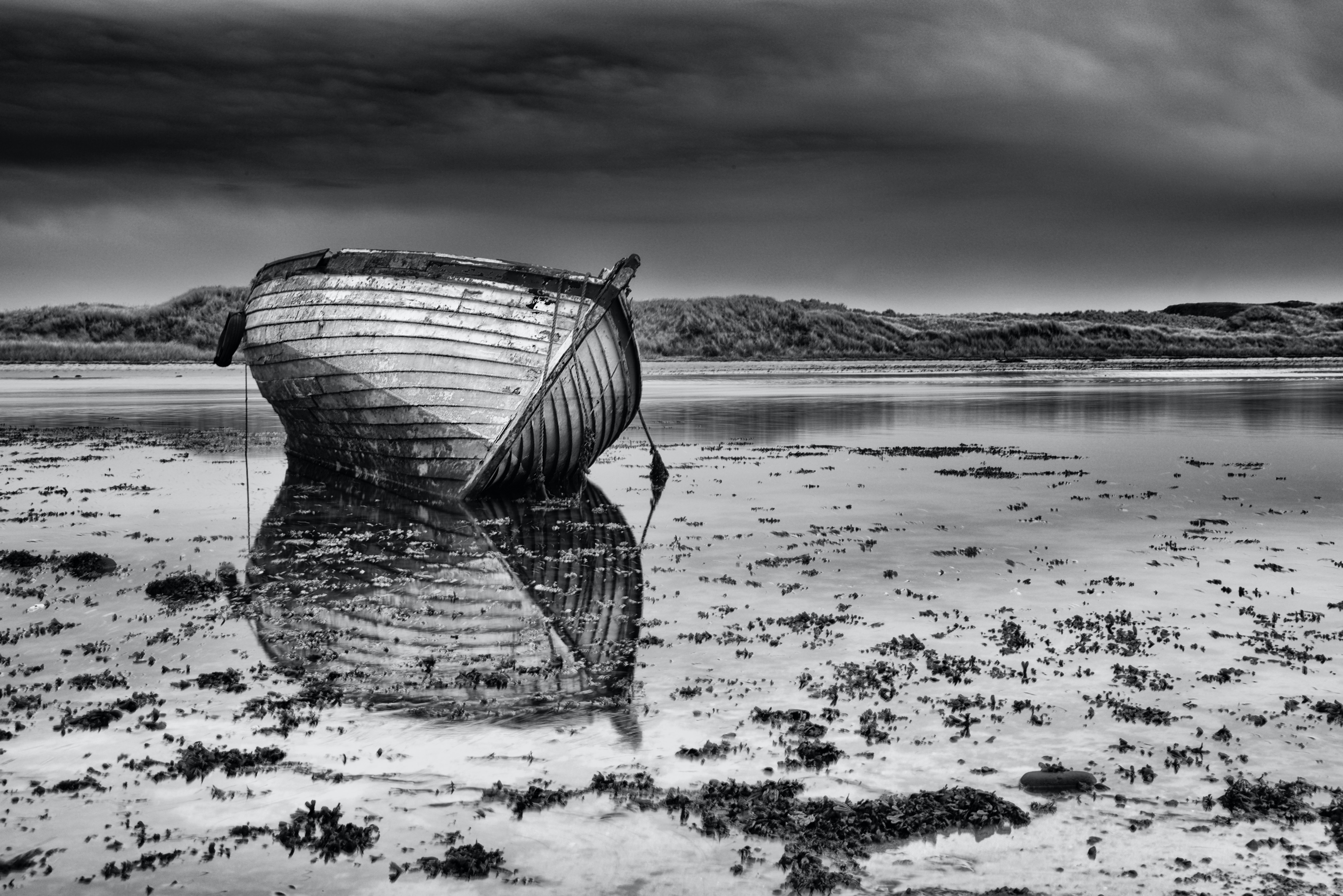 grayscale photograph of boat on mud