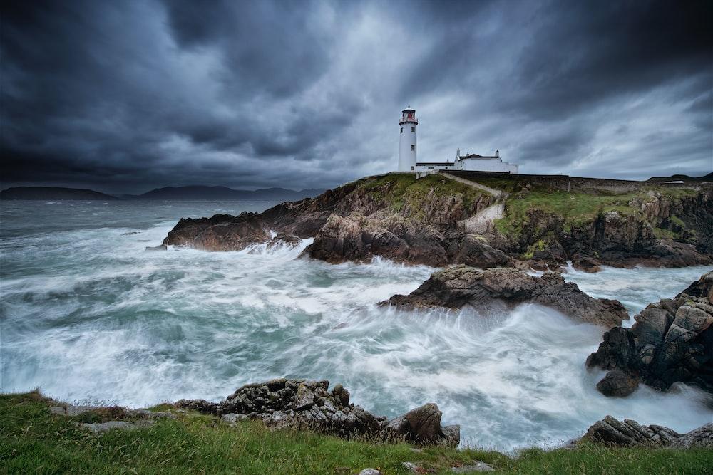 timelapse photograph of lighthouse on cliff near beach