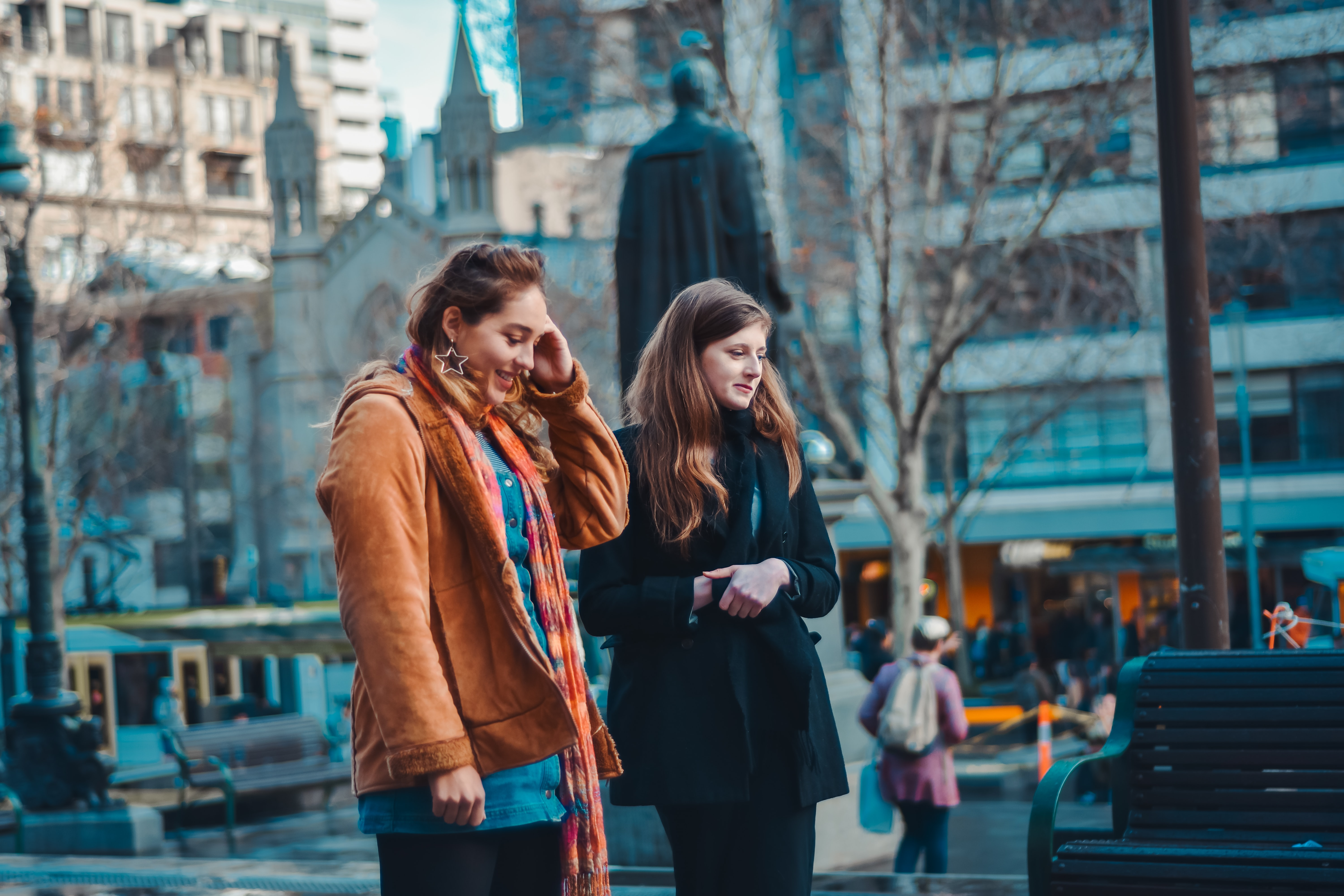 shallow focus photography of two women walking next to each other