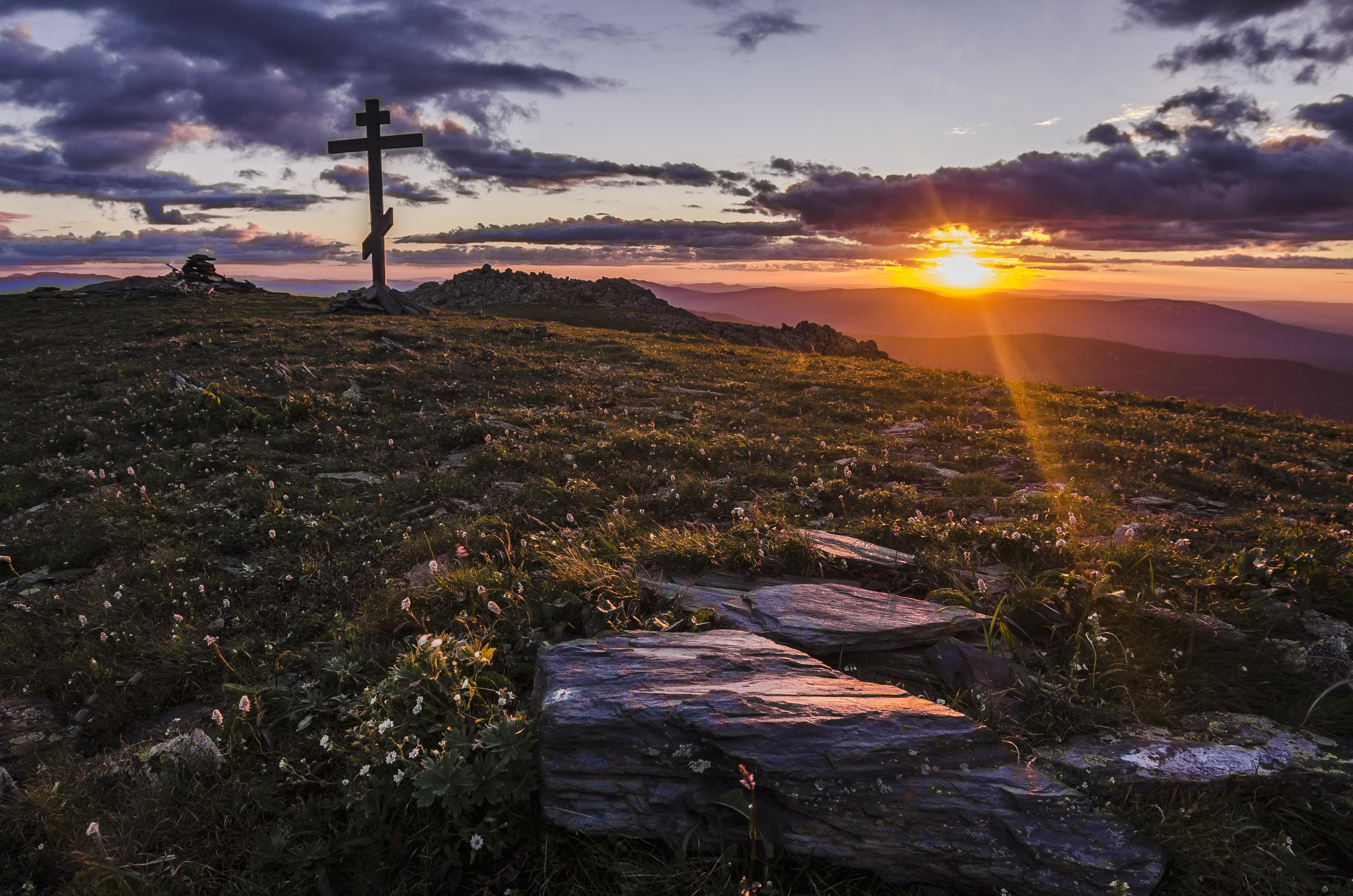 cross in an open field by the setting of sun