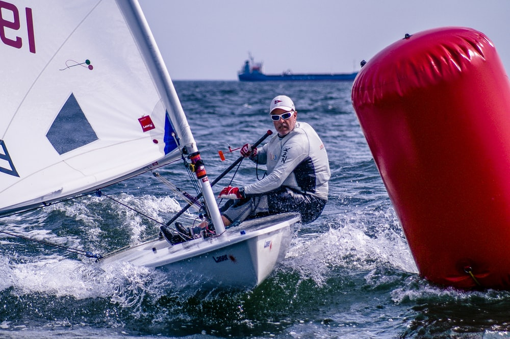man riding on sailboat near red float during daytime