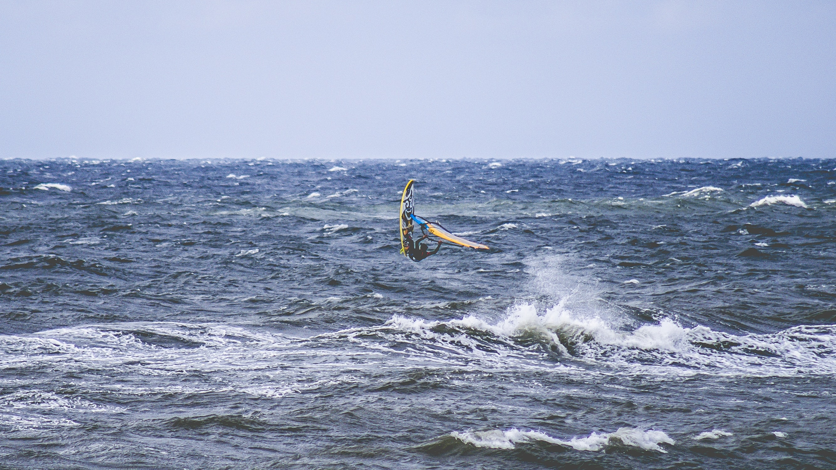 man surfing above body of water