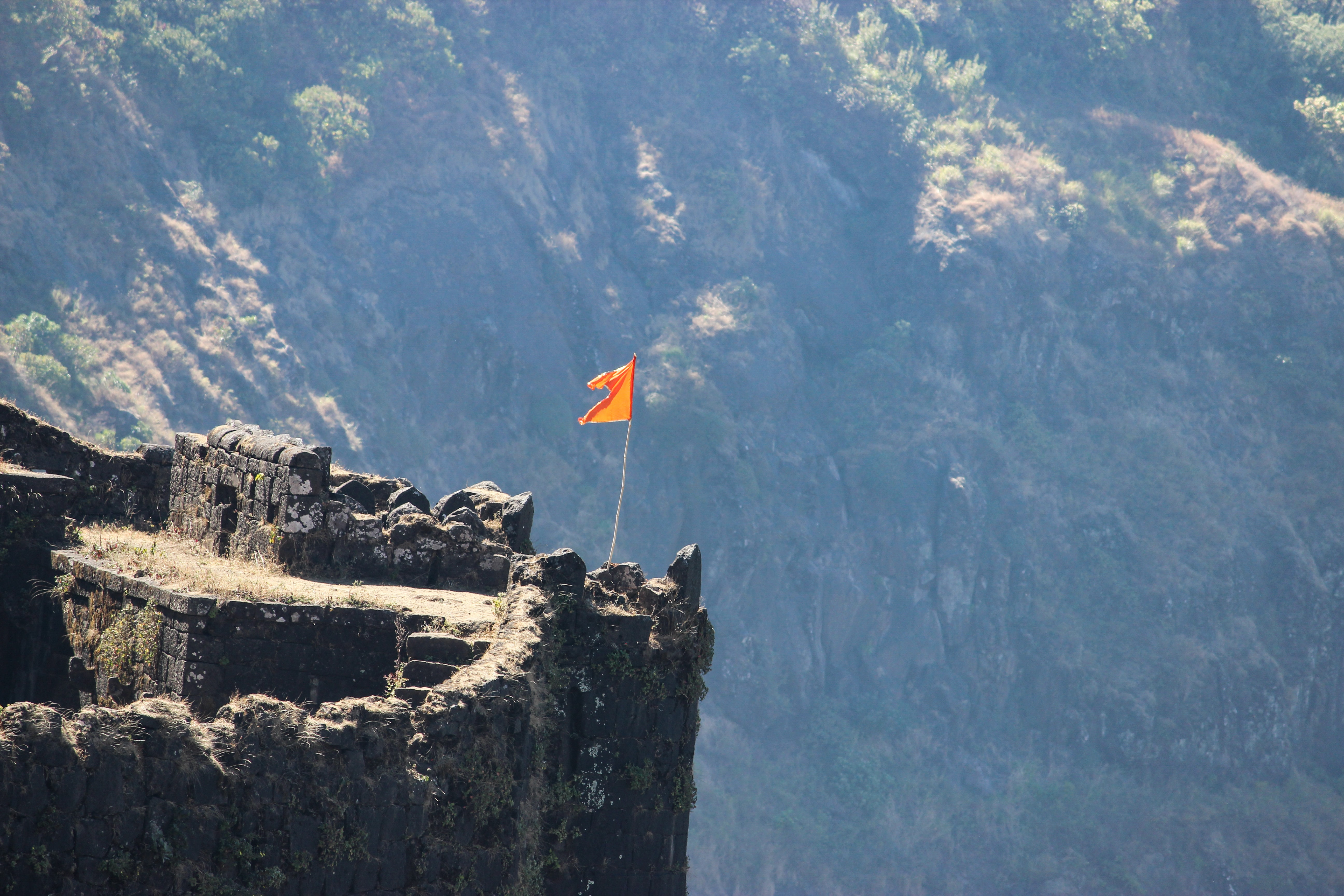 photo of flag stands on cliff
