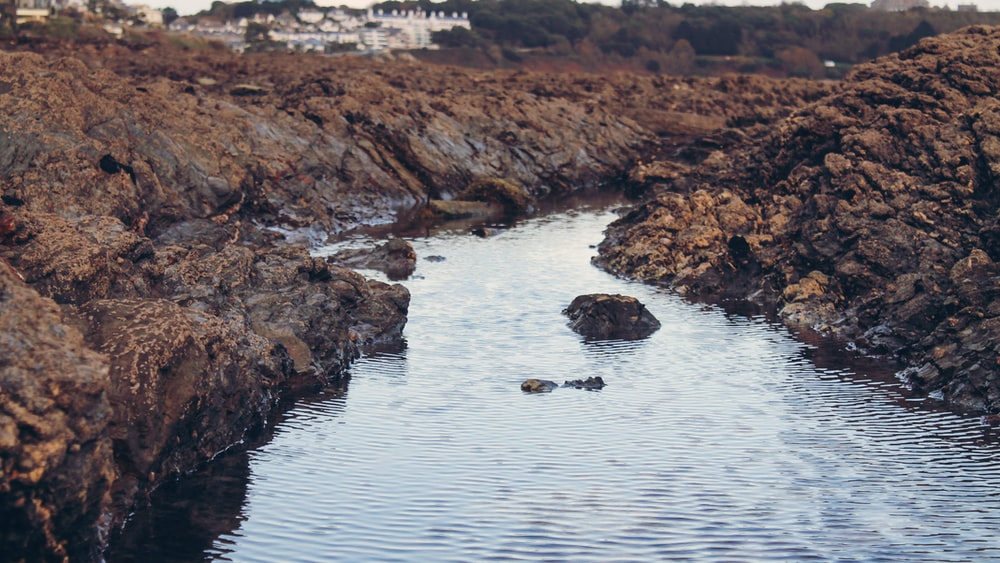 photo of body of water surrounded by rocks