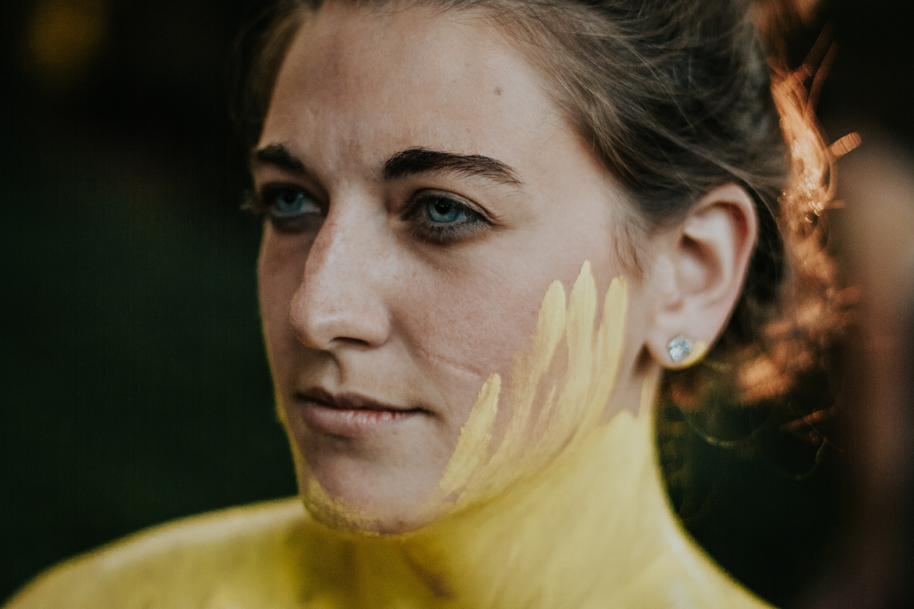 woman looking sideways with yellow paint on face