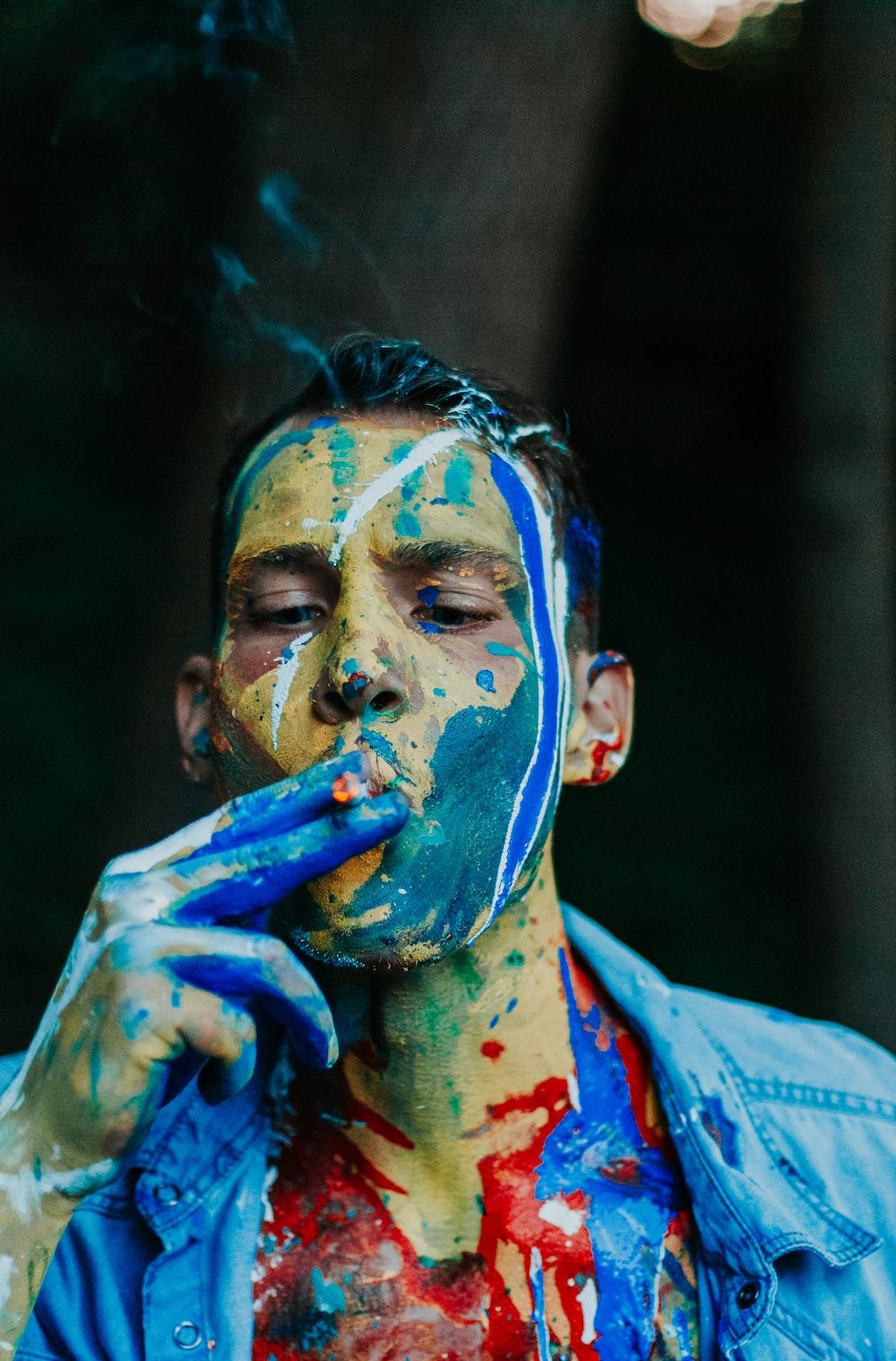 man wearing blue shirt while smoking