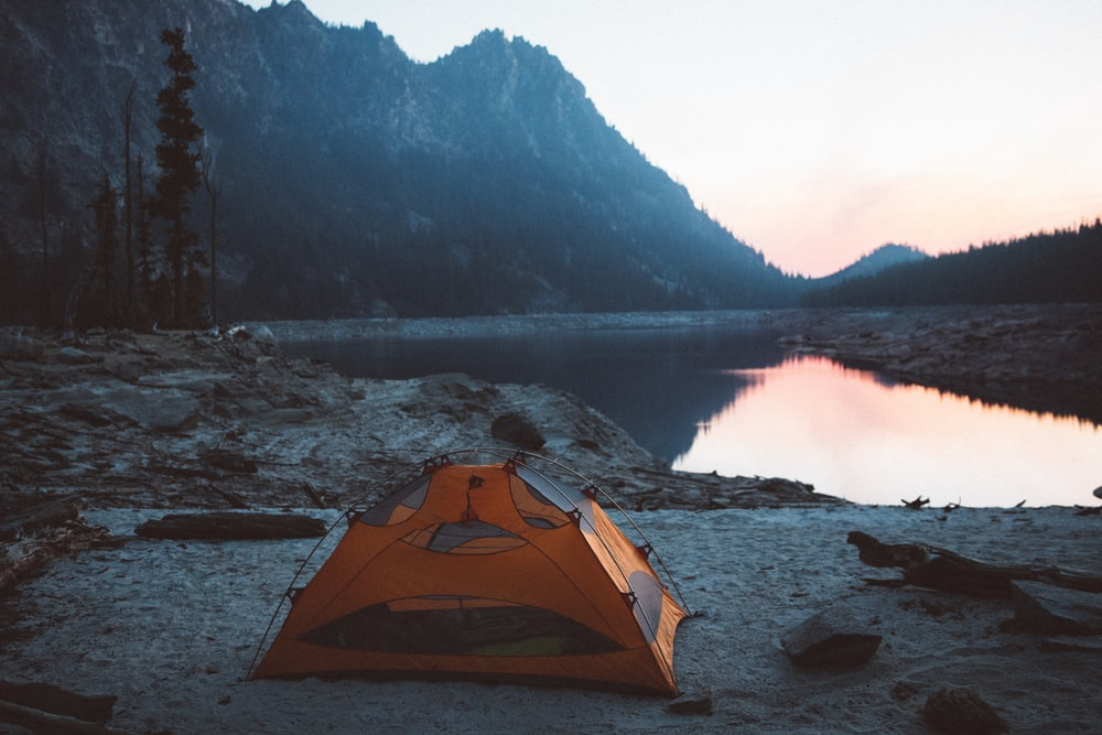 orange and gray camping tent near body of water