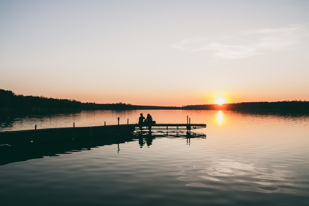 silhouette of two person sitting on dock during golden hour