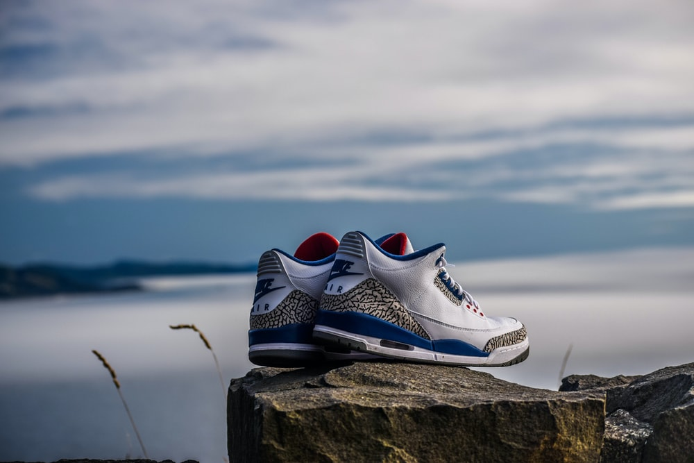 pair of white-and-blue Air Jordan 2's on rock fragment