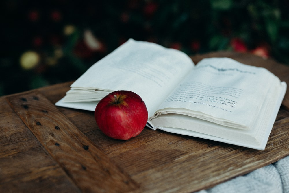 red apple beside opened book