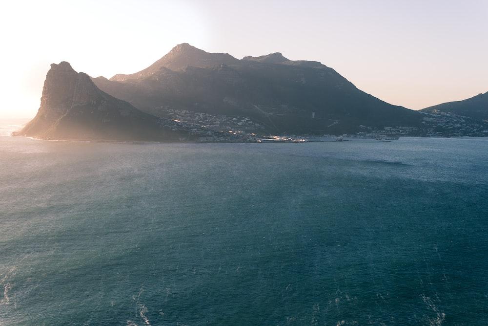 photo of mountain near body of water