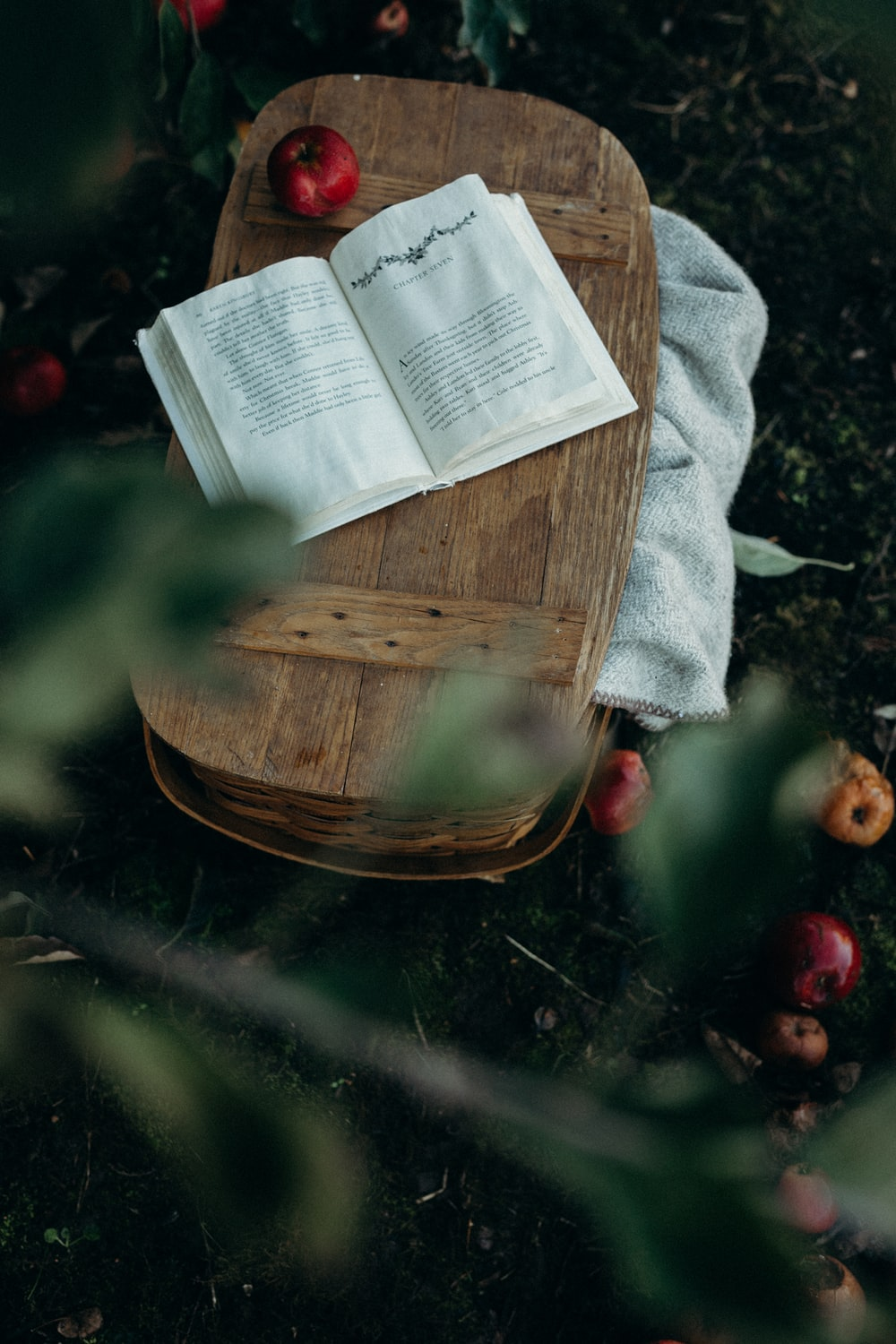 white book on top of brown picnic basket