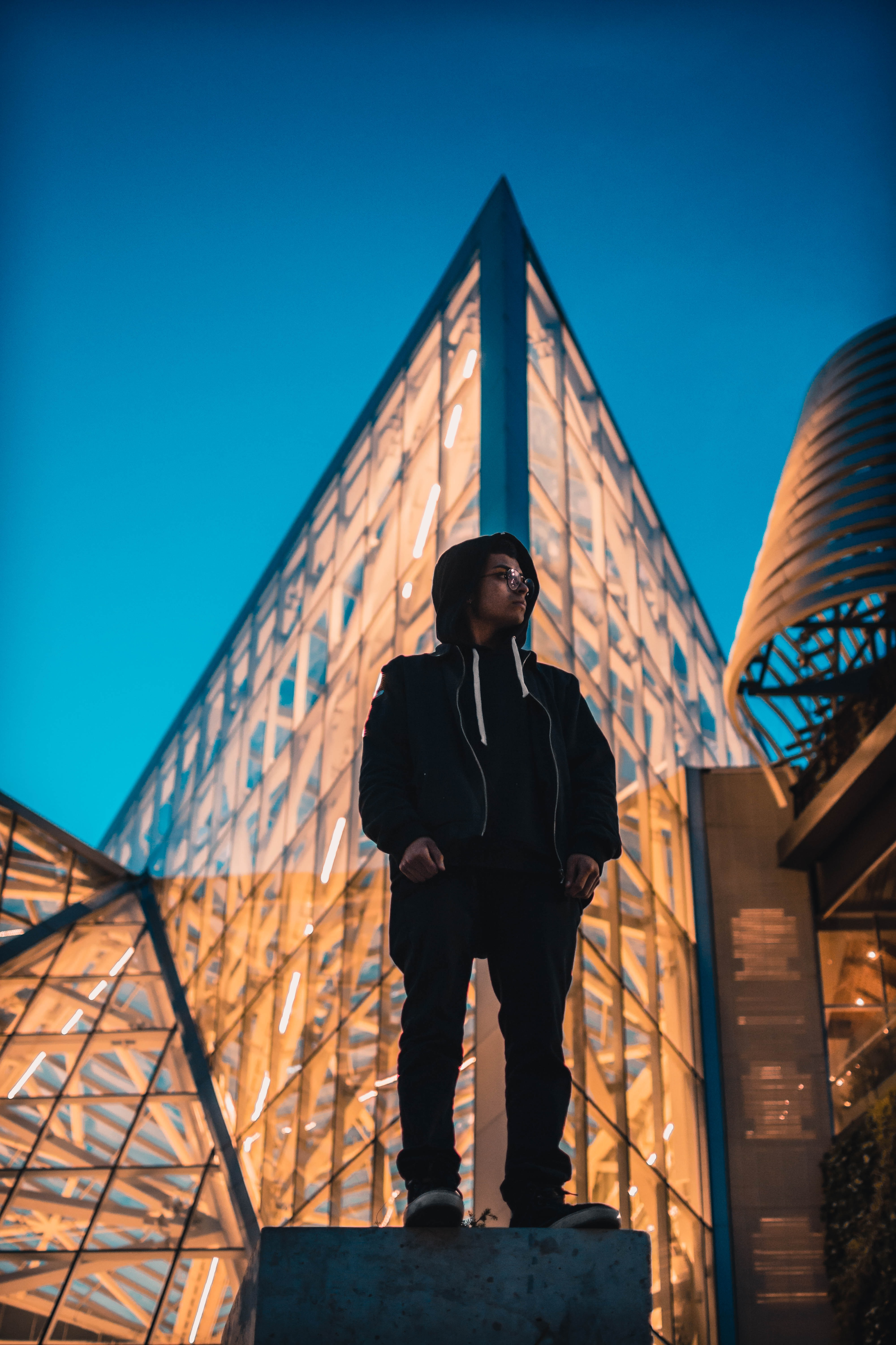 man standing front of curtain wall building at night time