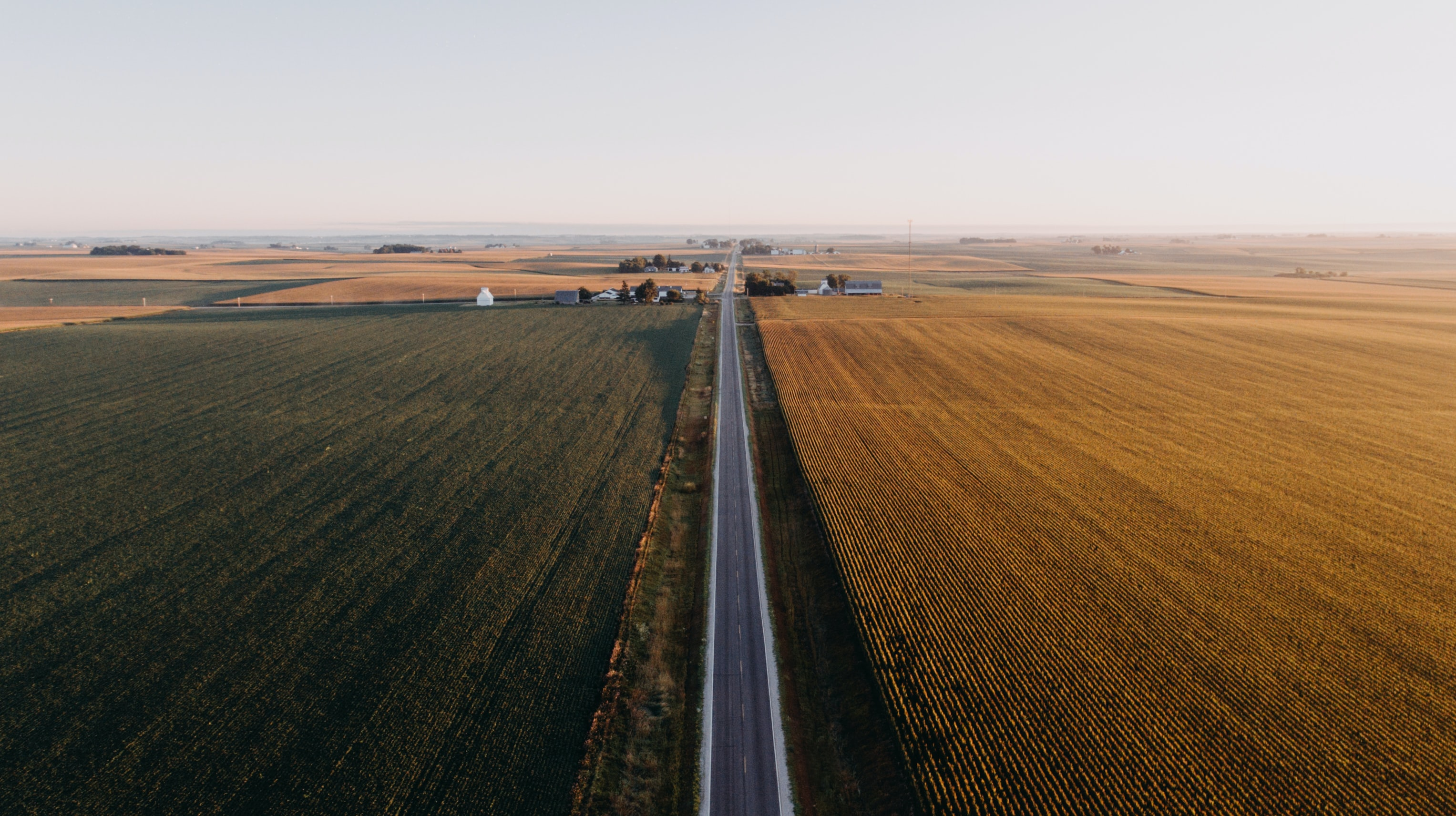 high angle view of gray roadway surrounded by grass field