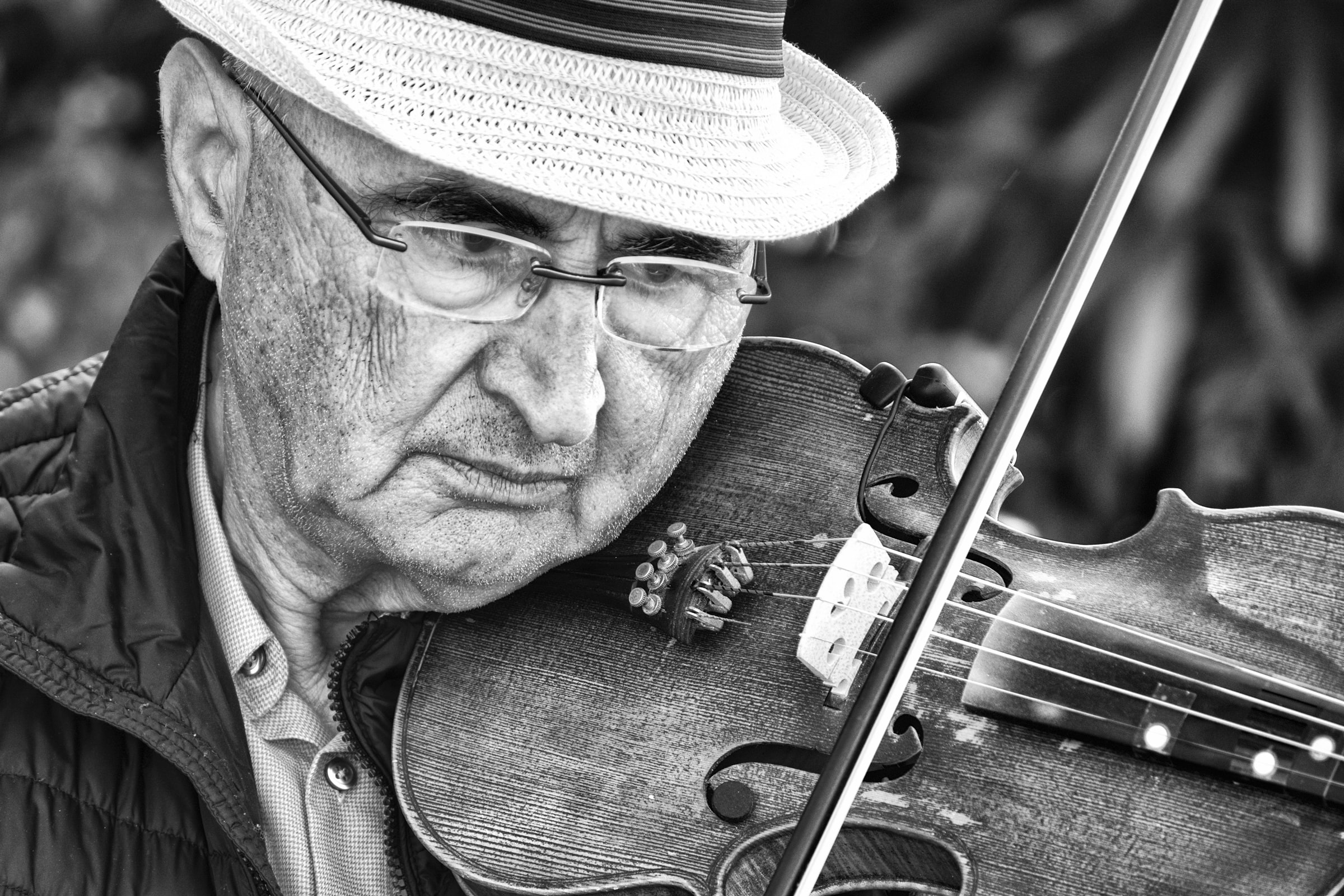 grayscale photography of man playing violin