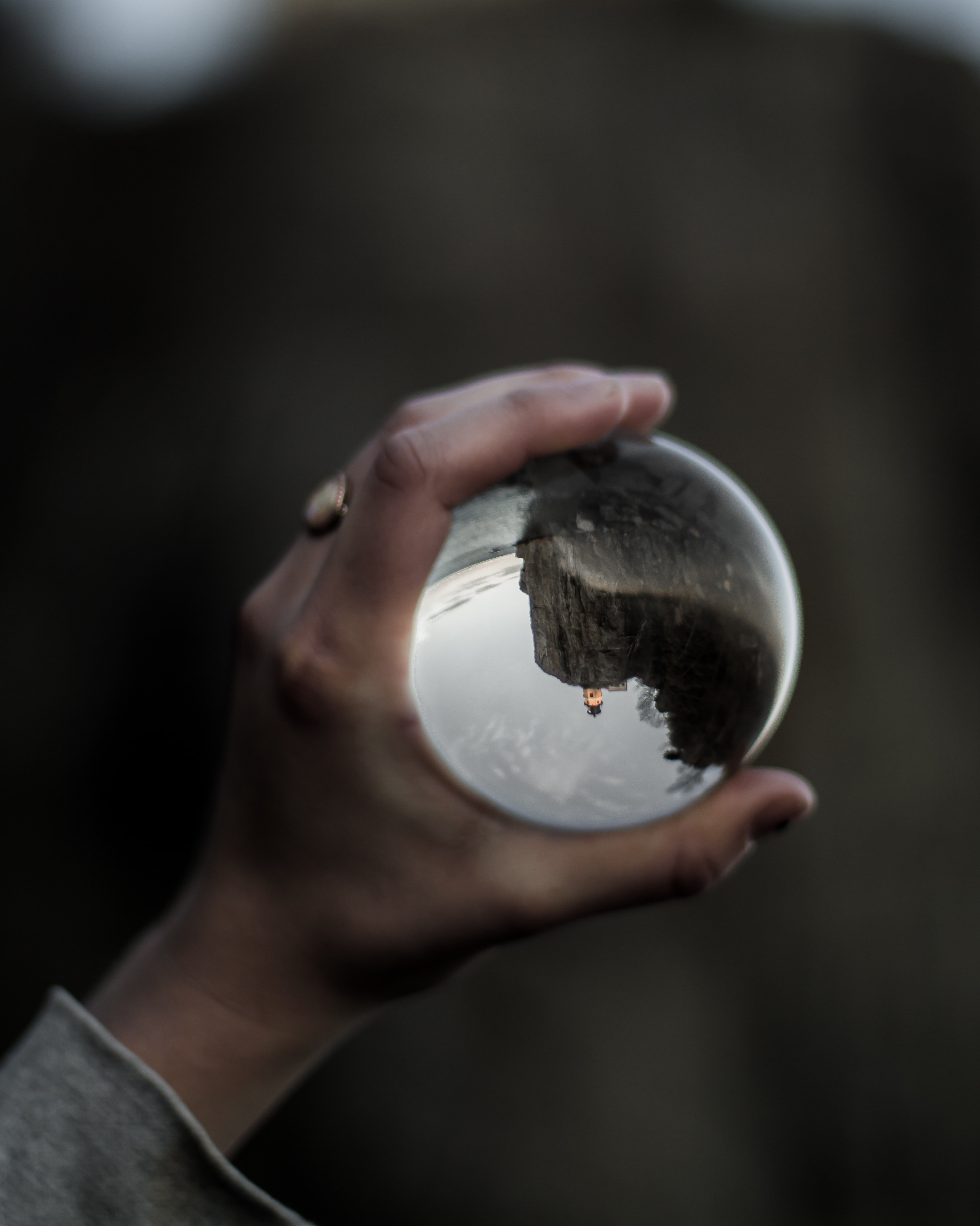 person holding clear glass water globe
