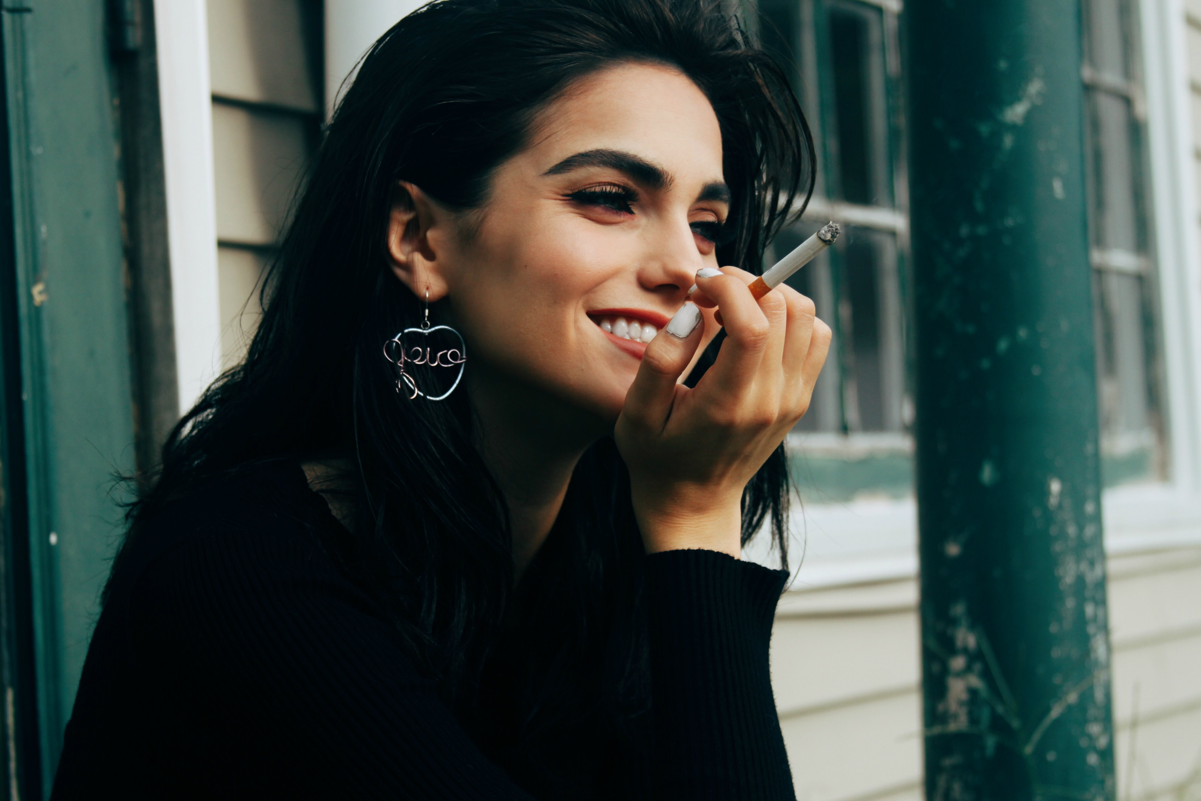 woman wearing black long-sleeved shirt holding lighted cigarette while smiling