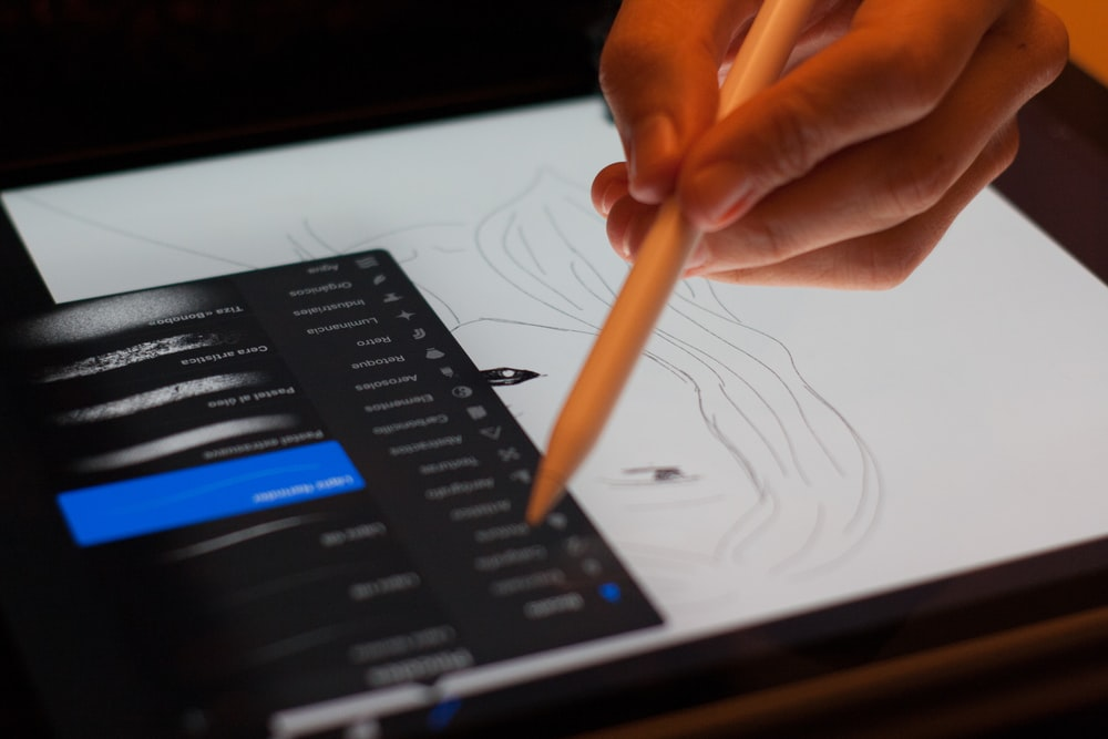 person holding stylus pointing on drawing pad