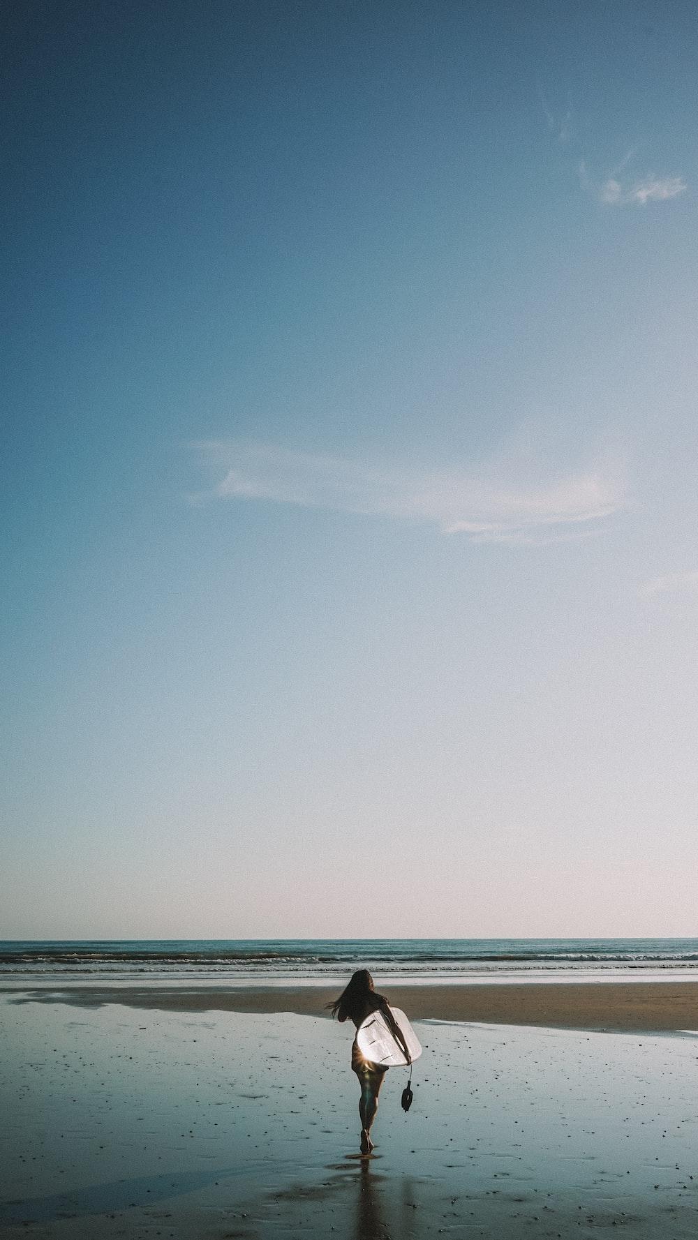 woman holding white surfboard walking on shore