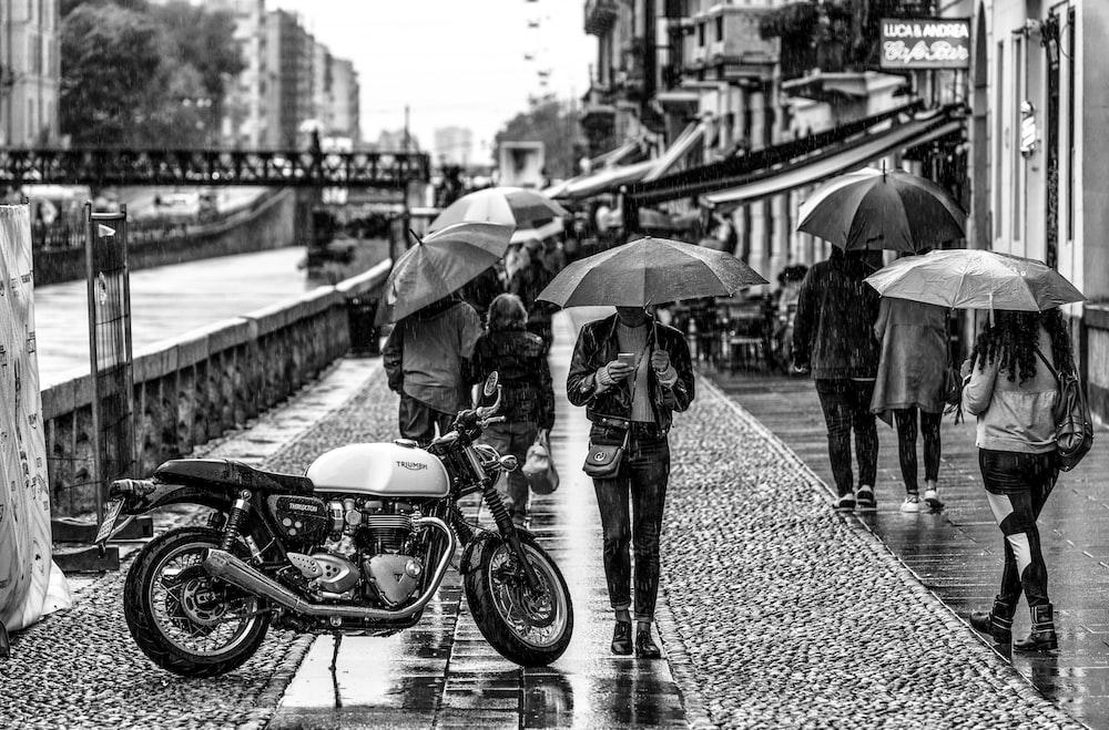 person under umbrella beside motorcycke