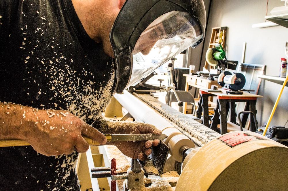 man wearing welding helmet in front of industrial machine
