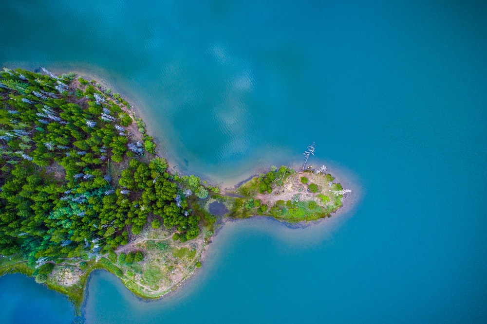 aerial photo of green and brown island and blue calm body of water at daytime