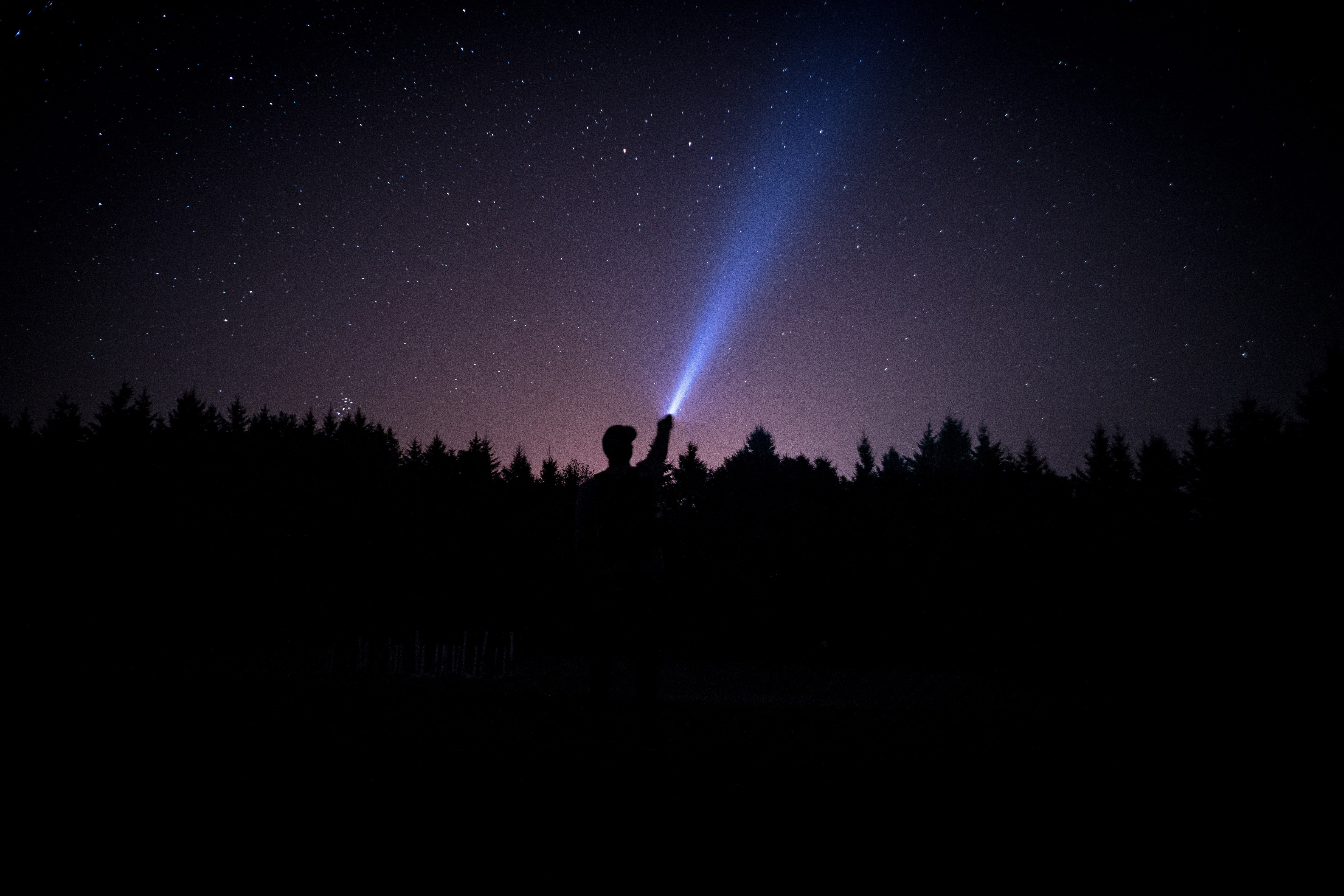 silhouette of person holding flashlight during nighttime