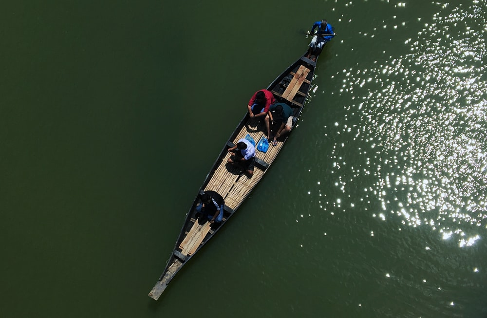person riding boat on body of water at daytime