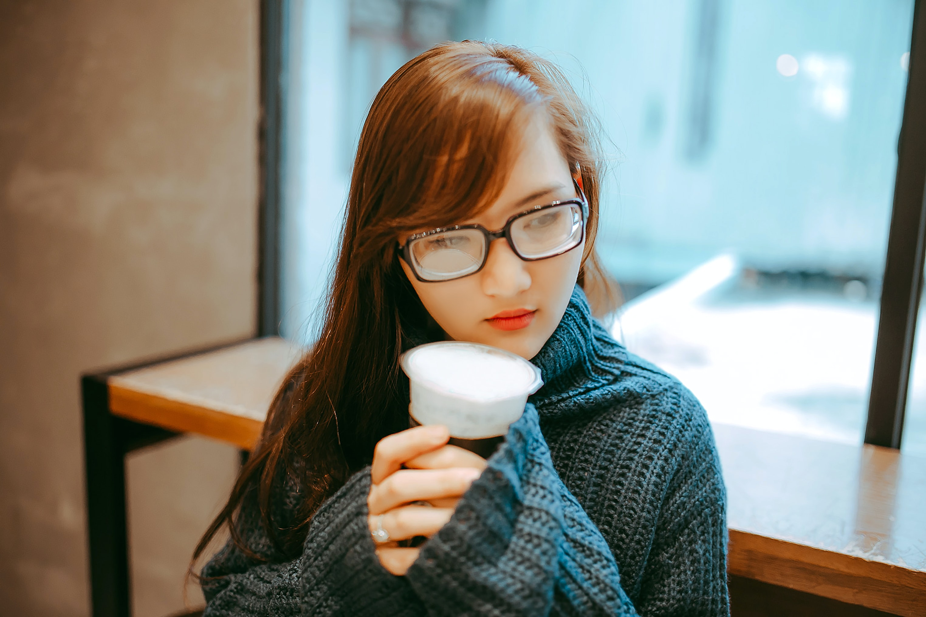 woman in gray knit jacket holding cup