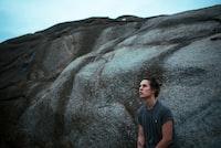 man wearing gray shirt leaning on rock