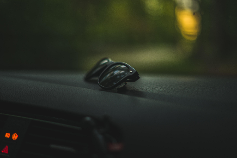 black sunglasses with black frames lying on car dashboard