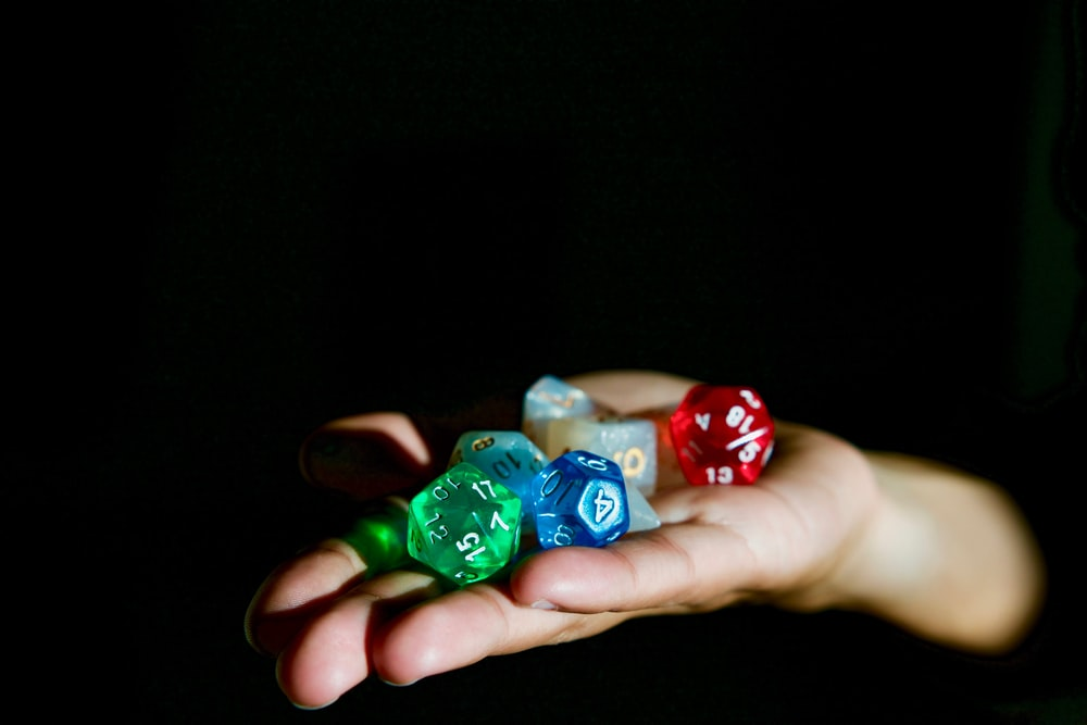 person holding polygonal die