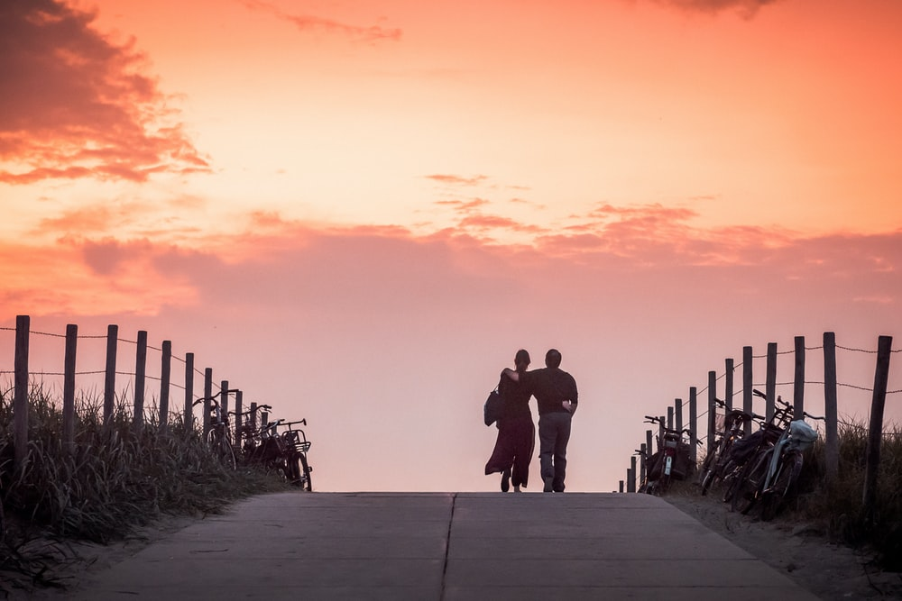 man and woman walking on road during dawn