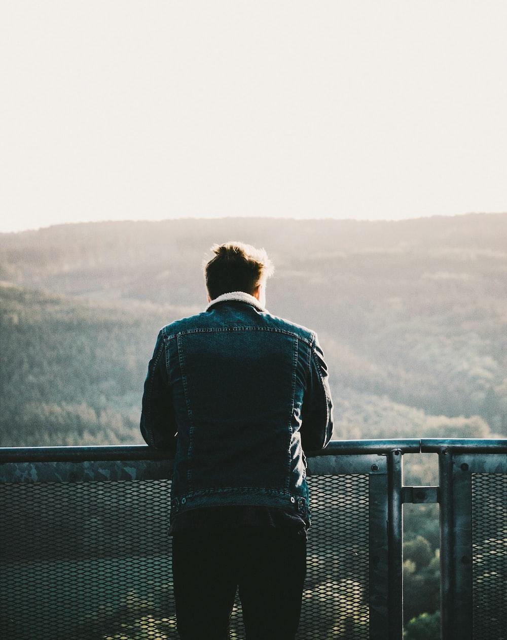man in green jacket looking at horizon during daytime