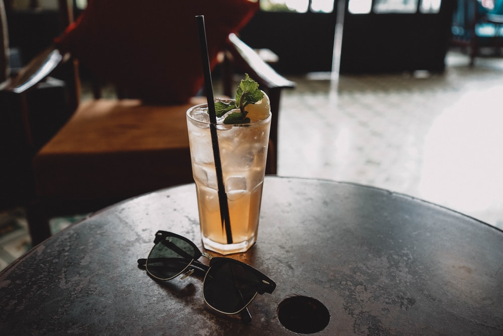 black Clubmaster-style sunglasses beside drinking glass