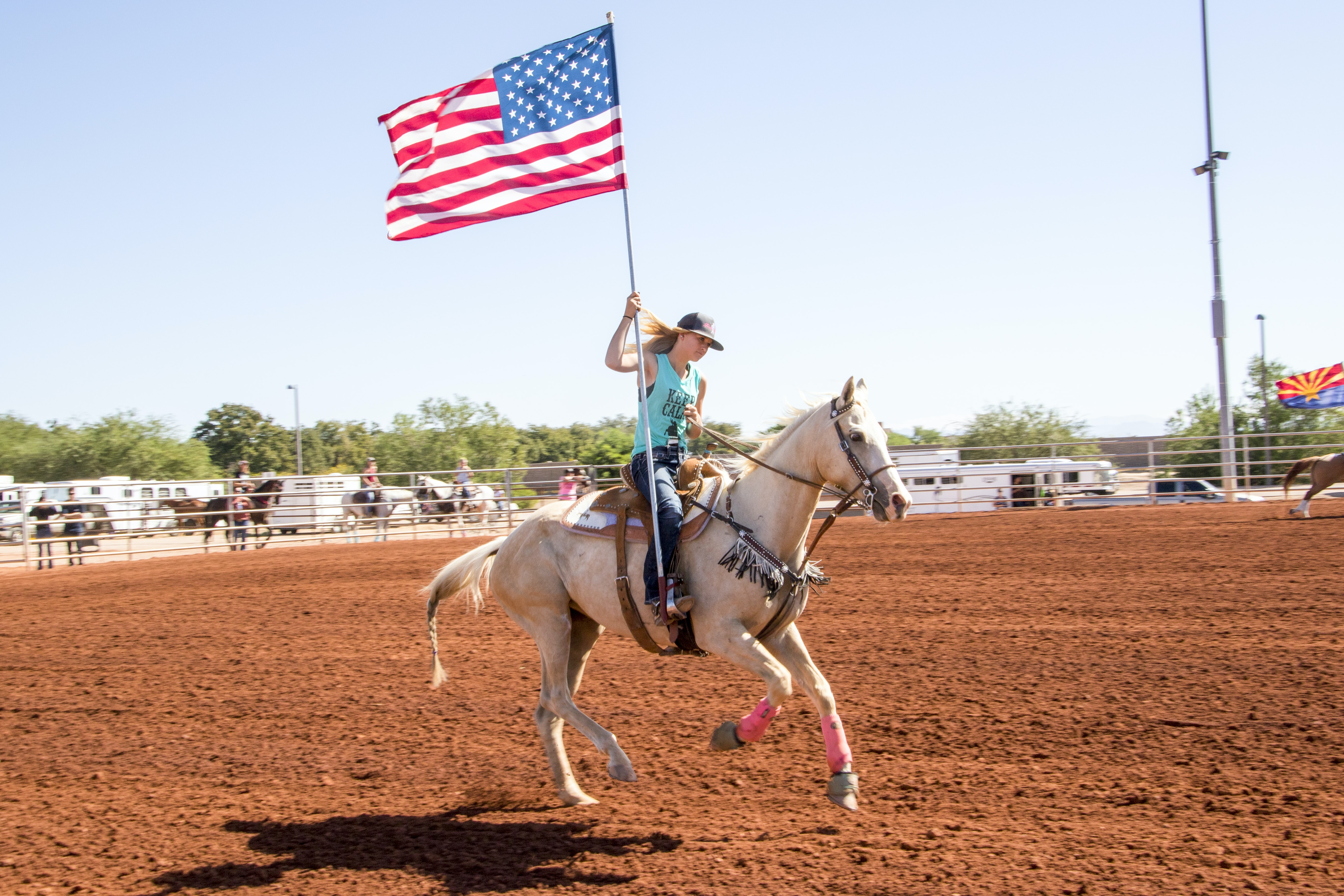 woman riding horse holding flag
