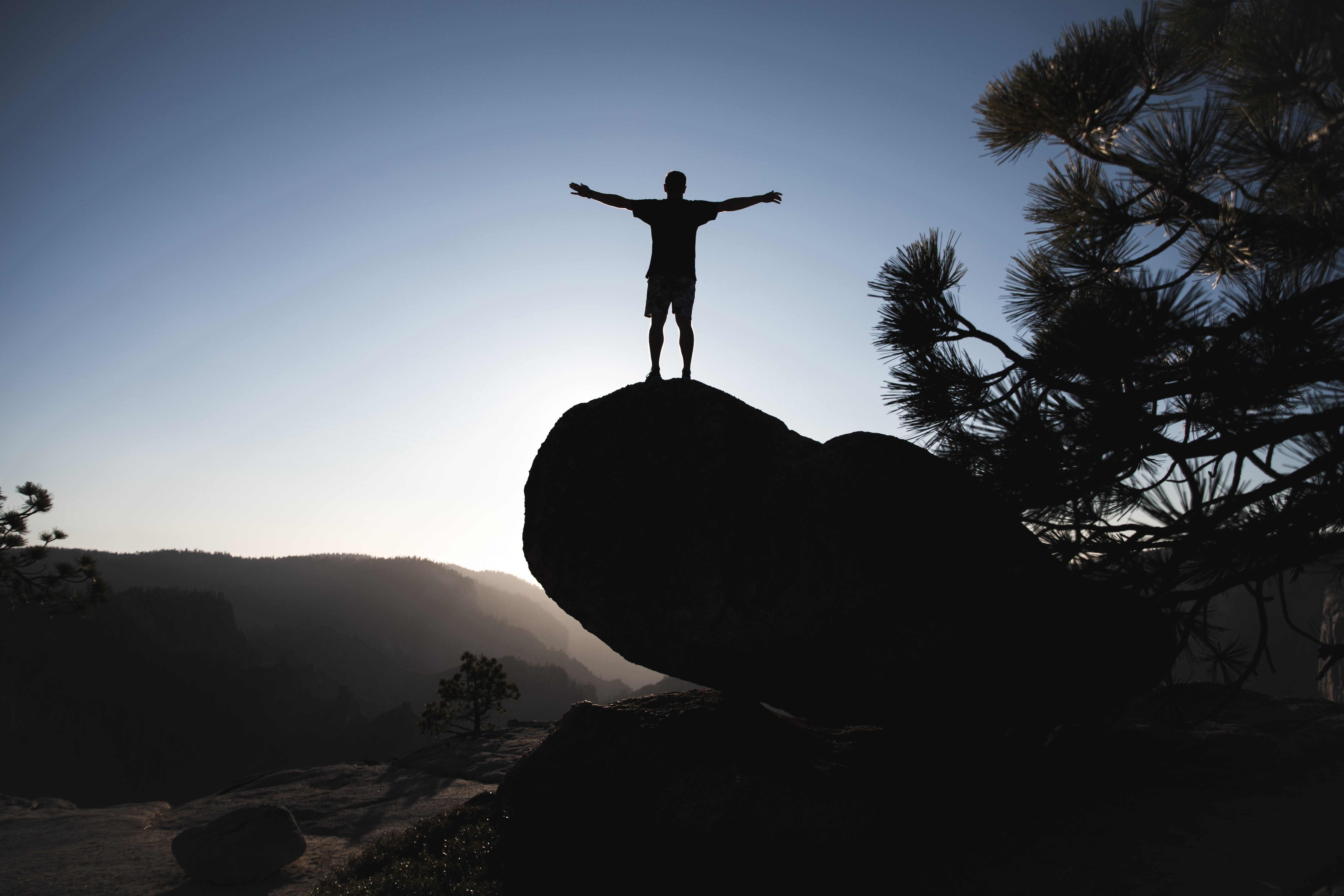 silhouette of man standing on boulder during daytime