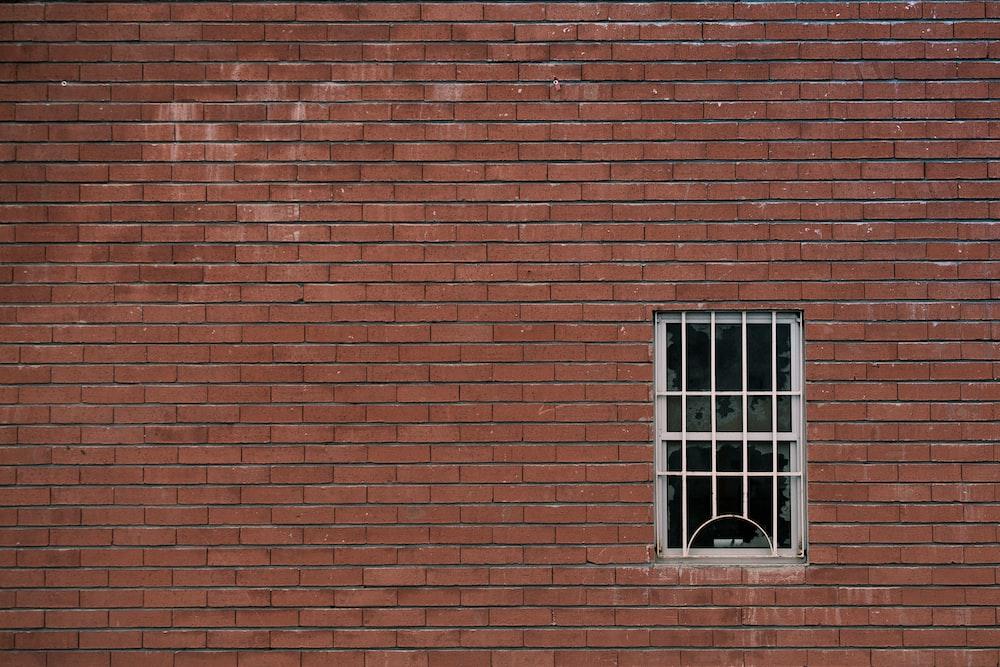 white window pane on brown concrete wall