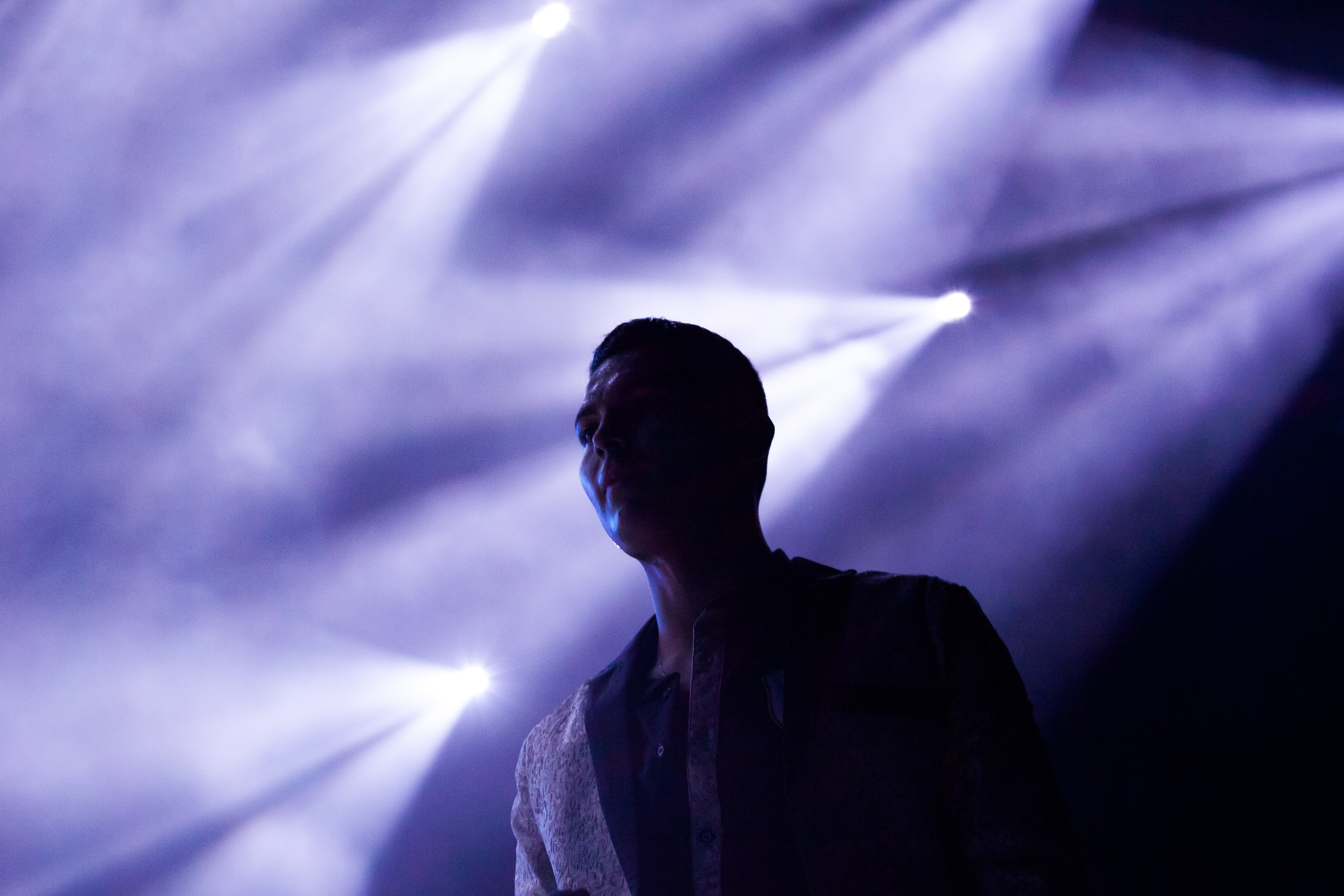 man's silhouette on stage reflected by stage lights