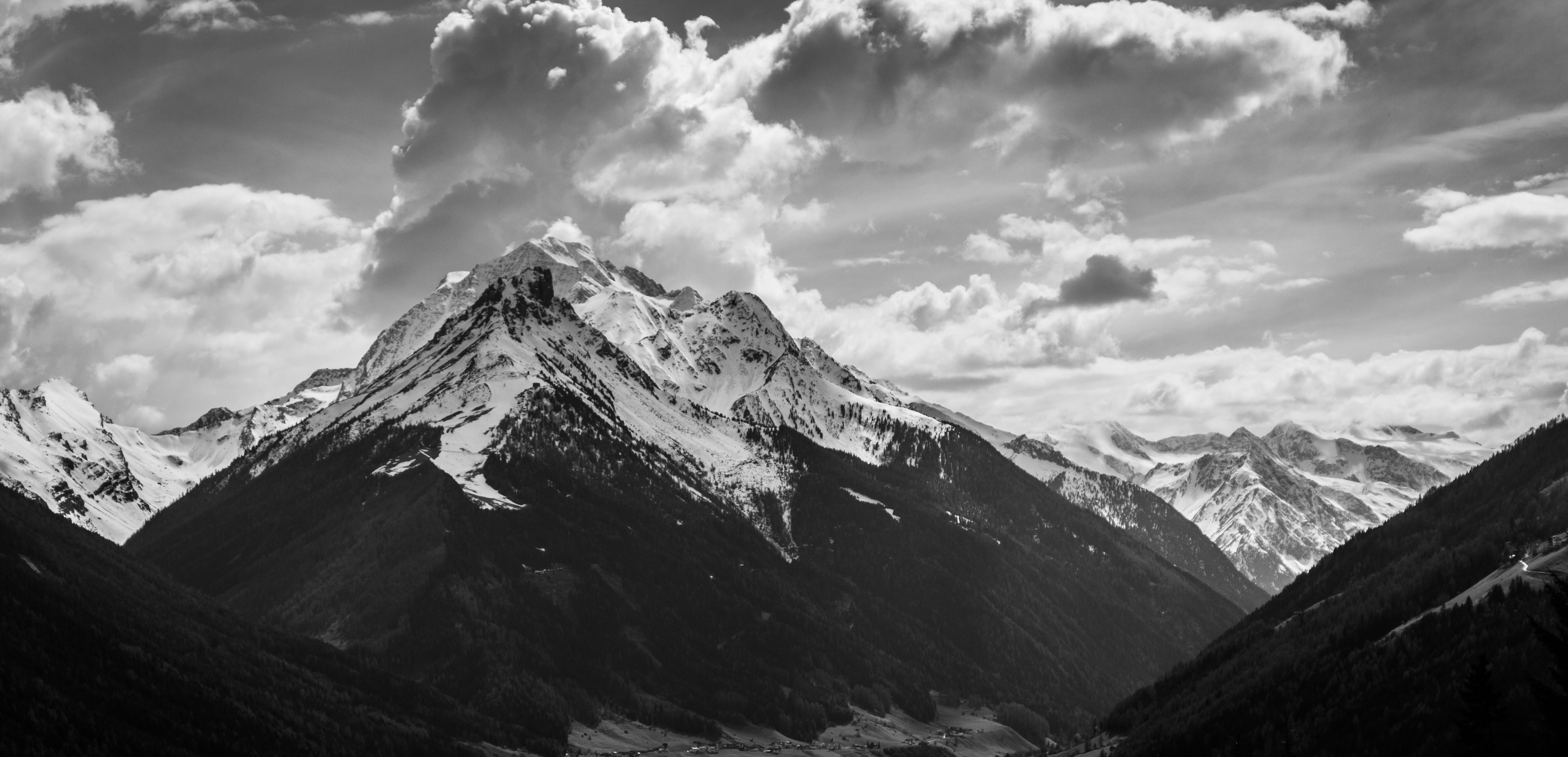 grayscale photo of mountain under clouds